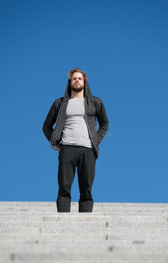 Atteignez pour le dessus Le type beau d'homme apprécient la promenade de matin sur le fond de ciel bleu d'escaliers Charge d'éner images libres de droits