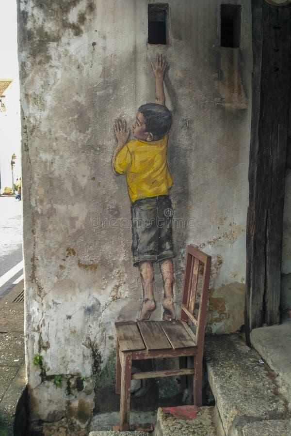 """Atteinte intitulée par peinture murale de rue """"""""peinte par Ernest Zacharevic à Penang le 6 juillet 2013 images libres de droits"""