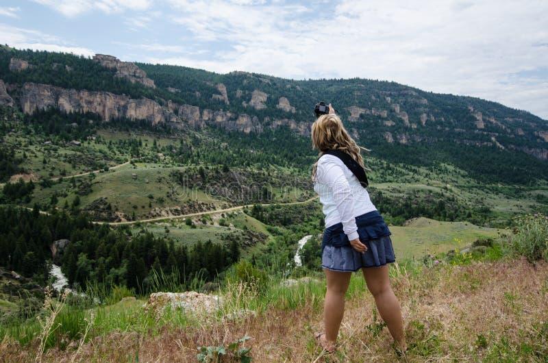 Attemps femelles blonds de photographe pour prendre une photo du paysage de montagne image stock