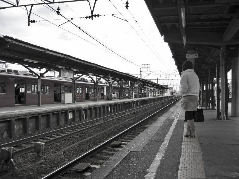 Attendendo in una stazione ferroviaria fotografia stock