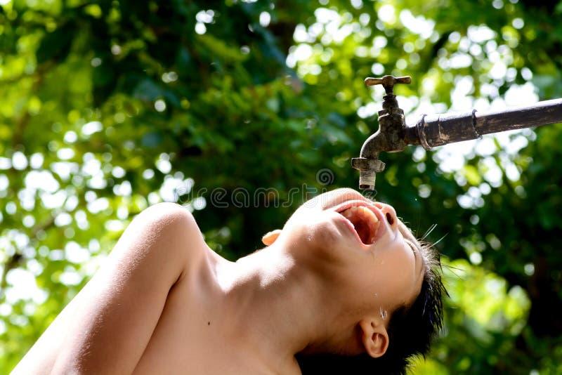 Attente de garçon l'eau du robinet images stock