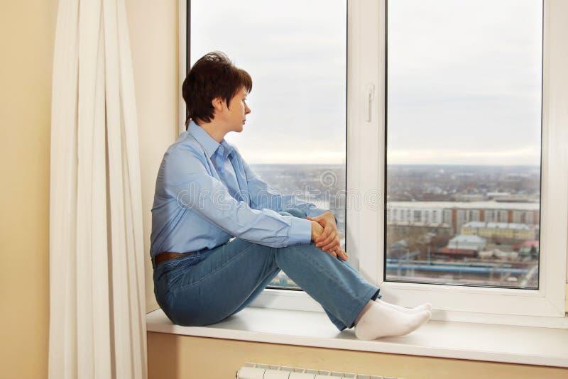 Attente de la femme s'asseyant sur un rebord de fenêtre photos libres de droits