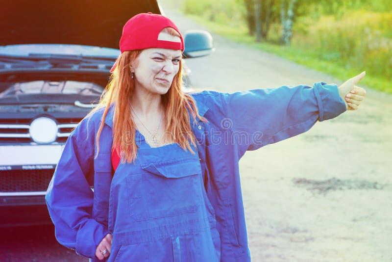Attente l'aide de bord de la route Portrait d'une jeune femme se tenant sur la route essayant d'arrêter la voiture demandant l'ai image libre de droits