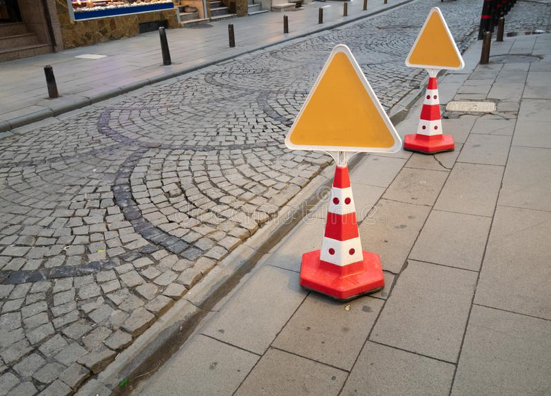 Attention orange cones with clear empty triangle signs. For no parking sidewalk pedestrian walk zone. city traffic regulation royalty free stock image