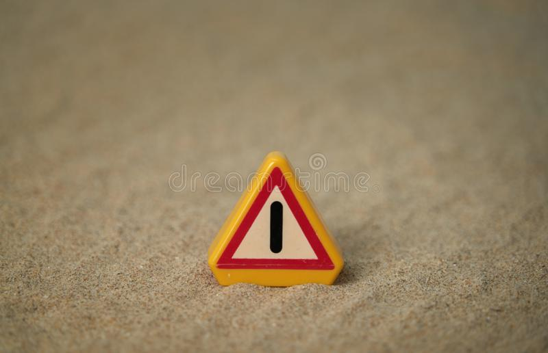 Attention signal on beach sand and with spaces around the motif to be able to put texts. Perfect for backgrounds. Blue, sky, warning, work, cone, white, orange royalty free stock photography