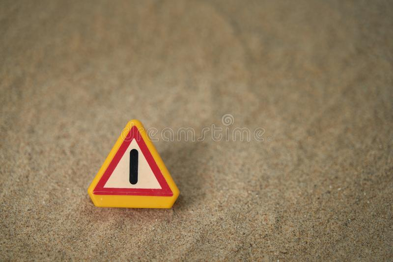 Attention signal on beach sand and with spaces around the motif to be able to put texts. Perfect for backgrounds. Blue, sky, warning, work, cone, white, orange royalty free stock image