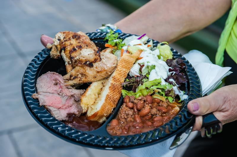 Attention to the details makes the party great. Hospitality accommodations feature a full plate of steak, chicken, salad, bread, and beans stock photos