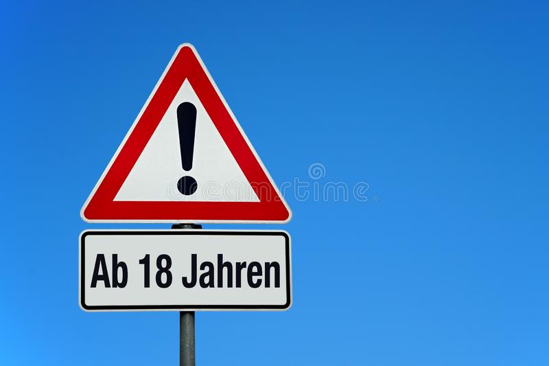 Attention and warning sign with blue sky and german text AB 18 JAHREN - translation: 18plus. With copy space royalty free stock photos