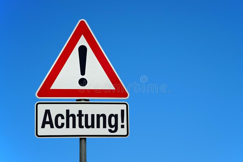 Attention and warning sign with german text ACHTUNG - translation: attention. Attention and warning sign with blue sky and german text ACHTUNG - translation royalty free stock photography