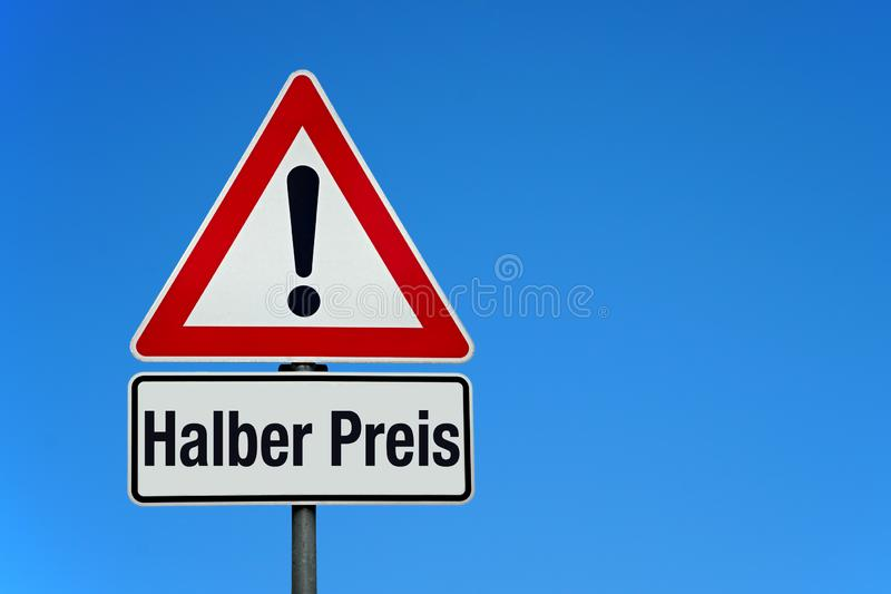 Attention and warning sign with blue sky and german text HALBER PREIS - translation: half price. With copy space royalty free stock images