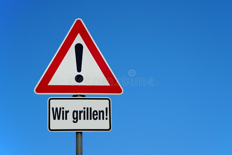 Attention and warning sign with blue sky and german text WIR GRILLEN - translation: we are grilling. With copy space royalty free stock photography