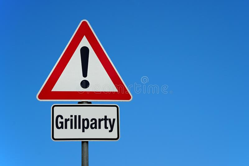 Attention and warning sign with german text GRILLPARTY - translation: barbecue party. Attention and warning sign with blue sky and german text GRILLPARTY royalty free stock photography