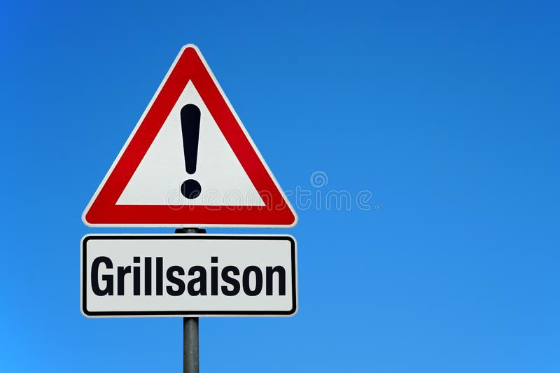 Attention and warning sign with german text GRILLSAISON - translation: barbecue season. Attention and warning sign with blue sky and german text GRILLSAISON stock photography