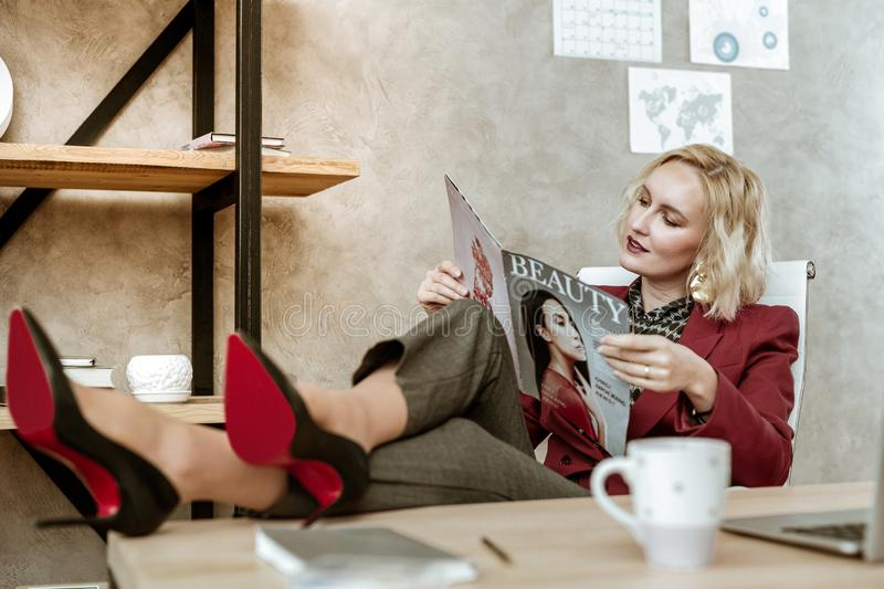 Attentive blonde attractive woman throwing legs on wooden table royalty free stock photography