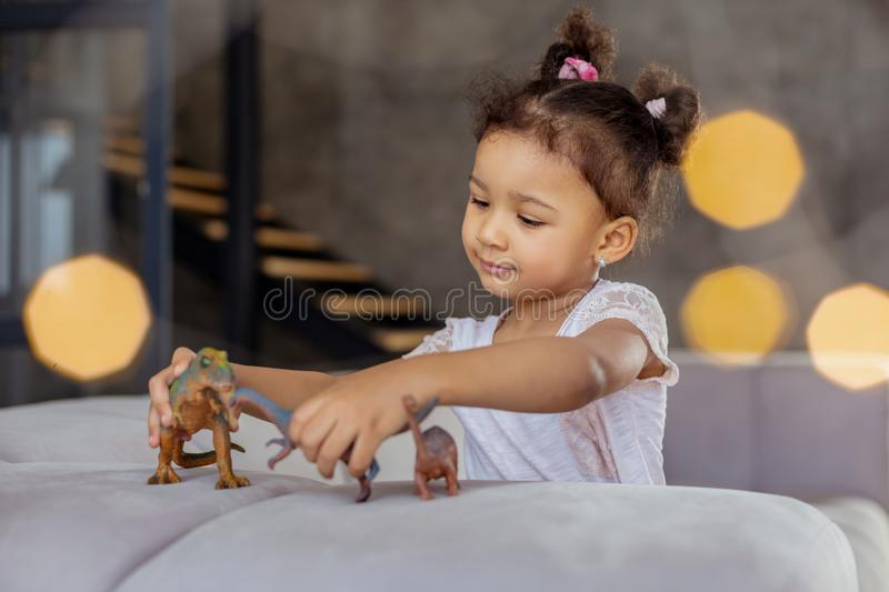 Attentive brunette kid playing with her dinosaurs. My toys. Concentrated little girl sitting on sofa and looking at her artificial animals royalty free stock images