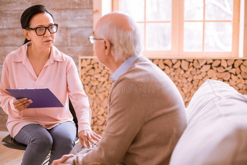 Attentive brunette woman looking at her interlocutor. Do not be sad. Pretty Asian female calming her patient, listening to his problems stock photo