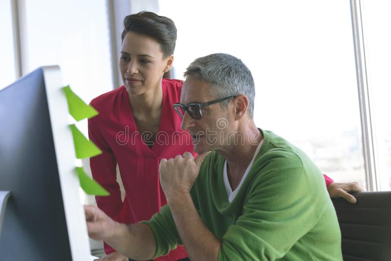 Attentive business people working at desk in creative office stock image