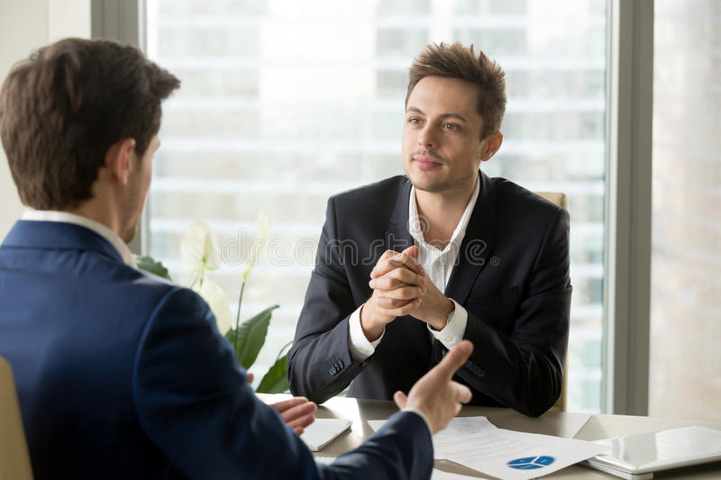 Attentive businessman listening to business partner talking duri royalty free stock photo