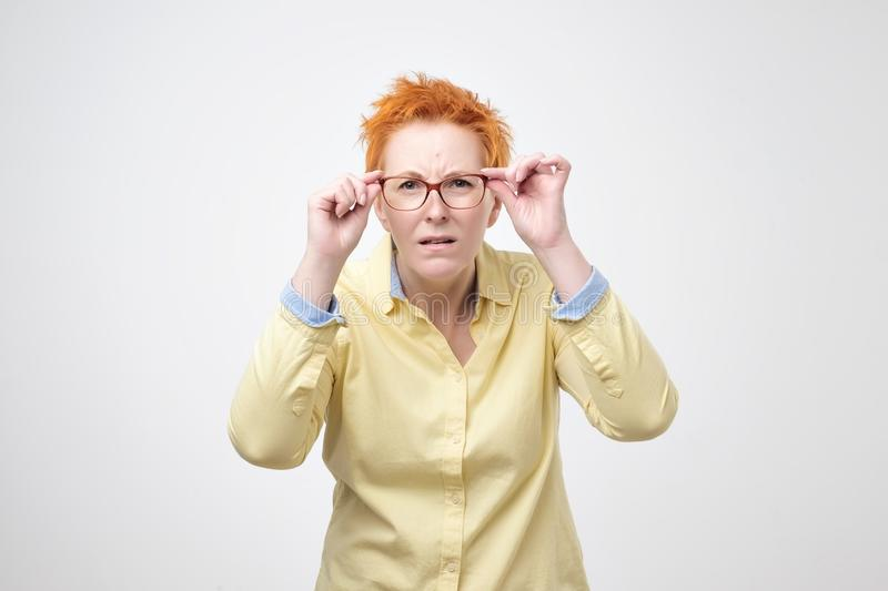 Attentive caucasian woman with short red hair looks scrupulously into distance, keeps hand on rim of spectacles. royalty free stock photos
