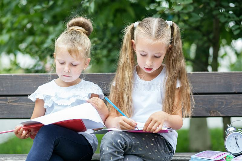 Attentive children draw in the schoolyard. The concept of school, study, education, friendship, childhood.  royalty free stock photo