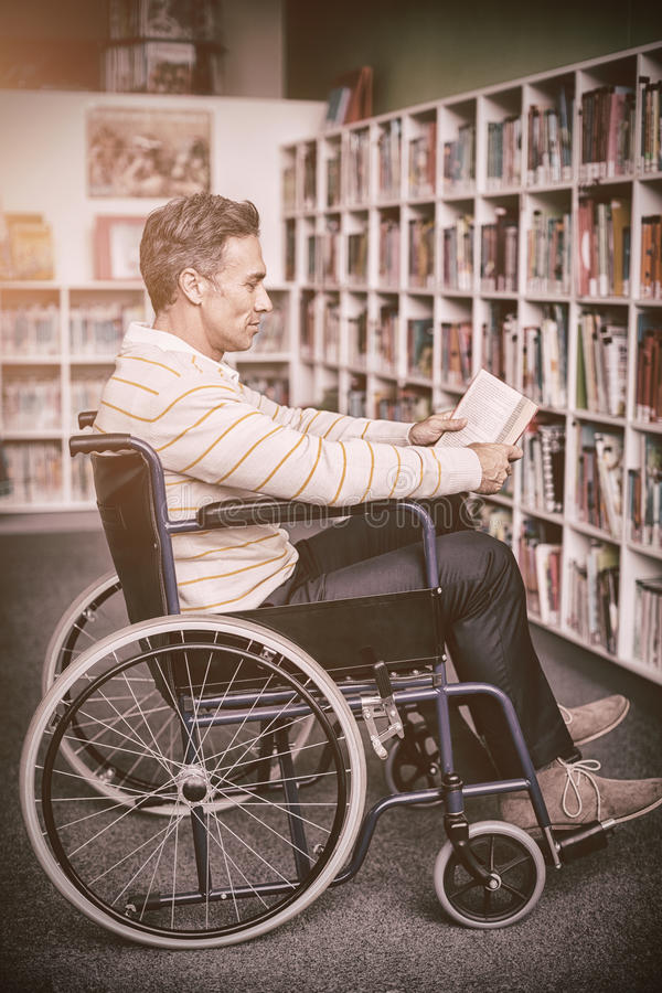 Attentive disabled school teacher reading book in library. At school stock illustration