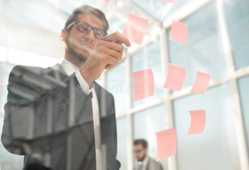Attentive employee reads a sticker-note on the office Board stock photo