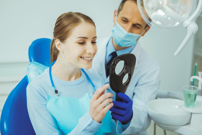 Attentive girl checking her teeth. Relaxed atmosphere. Pretty female smiling while visiting her dentist royalty free stock photography