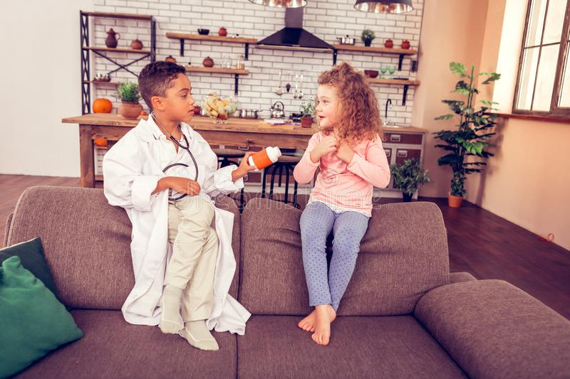 Attentive little male giving pills to his patient. Vitamins for you. Emotional girl expressing positivity while listening to her friend royalty free stock photography