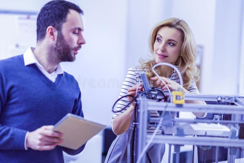 Attentive male person listening to his colleague. Machinery industry. Pleased blonde female keeping smile on her face while demonstrating test printer royalty free stock photography
