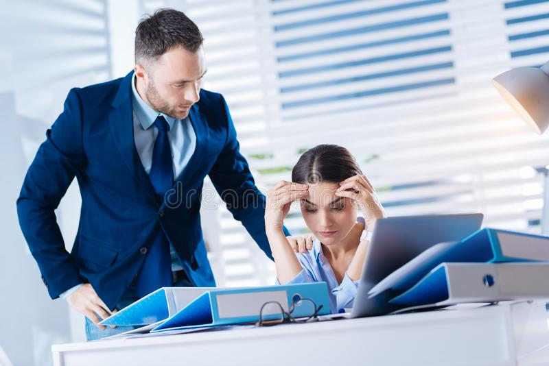 Attentive man looking at his colleague while noticing her bad condition. Be strong. Kind attentive caring men standing near his tired colleague sitting with her royalty free stock image
