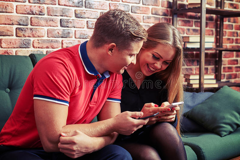 Attentive man looking at his girlfriend using smartphone stock images
