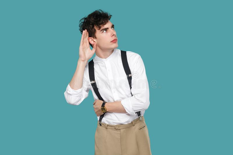Attentive man trying to hear with hand near ears stock photos