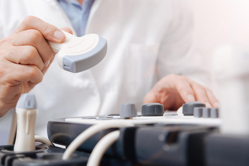 Attentive medic testing sonogram equipment in the clinic. High quality equipment . Skillful experienced confident doctor working in the clinic and using stock photos