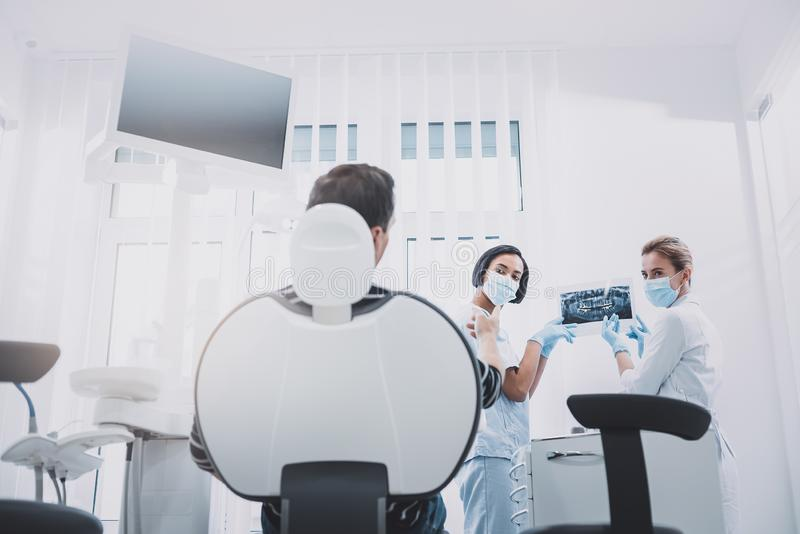 Attentive patient listening to his dentist and assistant stock photos