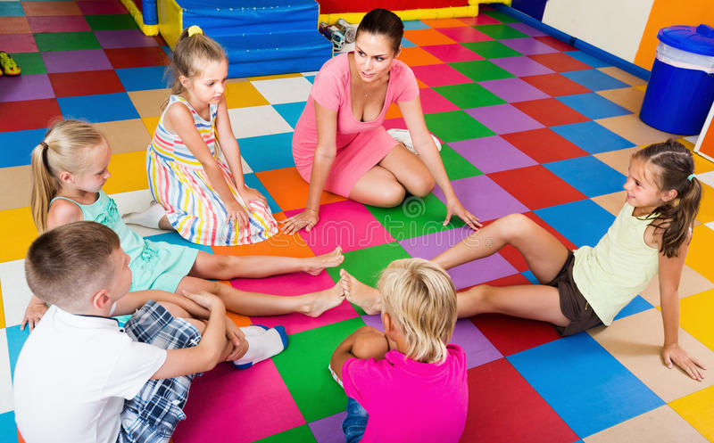 Attentive positive children sitting with teacher in classroom a stock photo