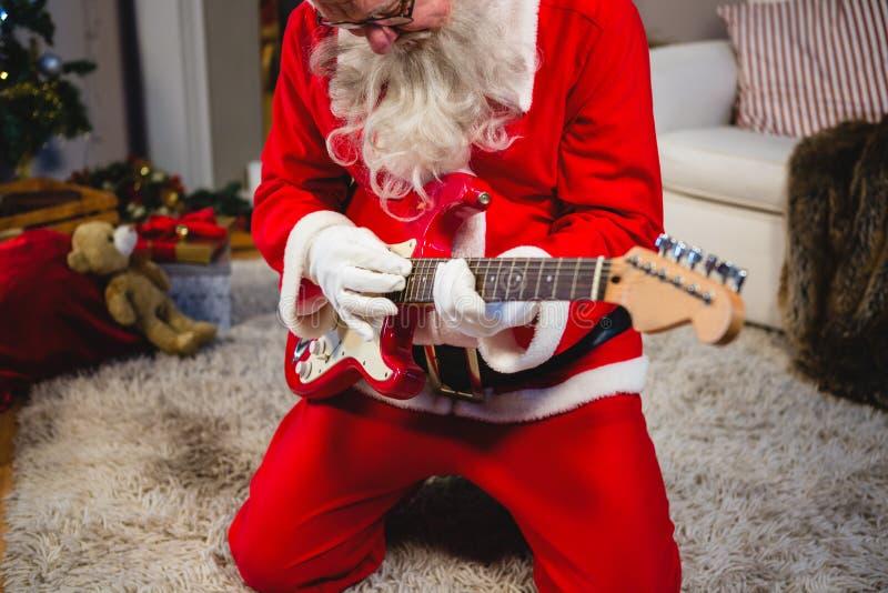 Attentive santa claus playing a guitar royalty free stock image