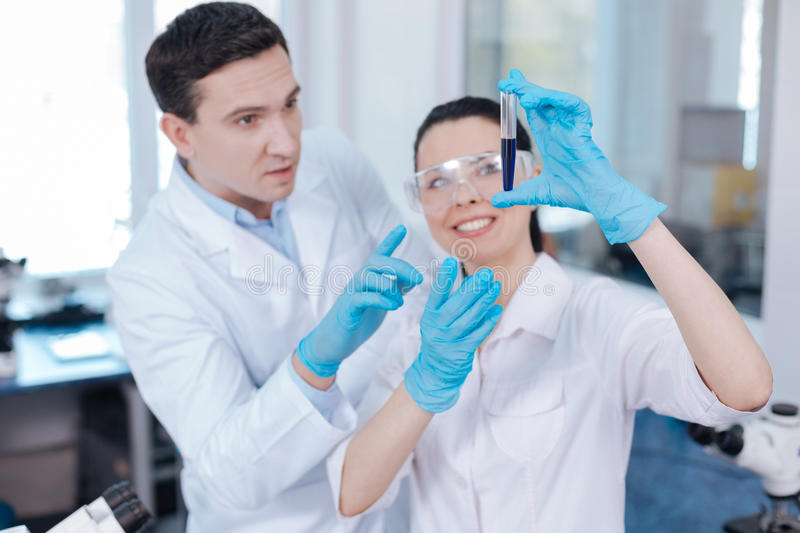 Attentive scientist giving remarks to his assistant. Case comment. Positive delighted female researcher keeping smile on her face and looking upwards while stock image