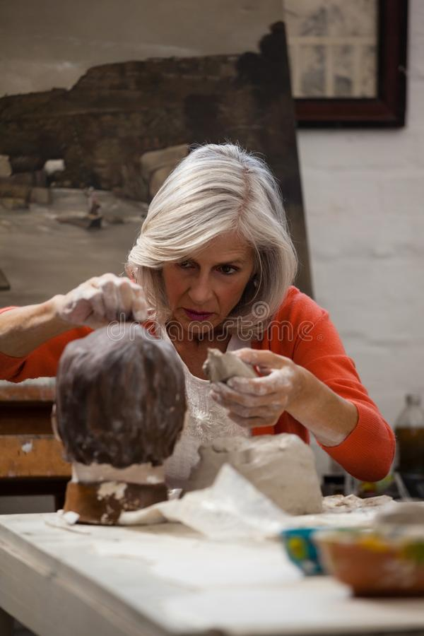 Attentive senior woman making a clay sculpture royalty free stock image