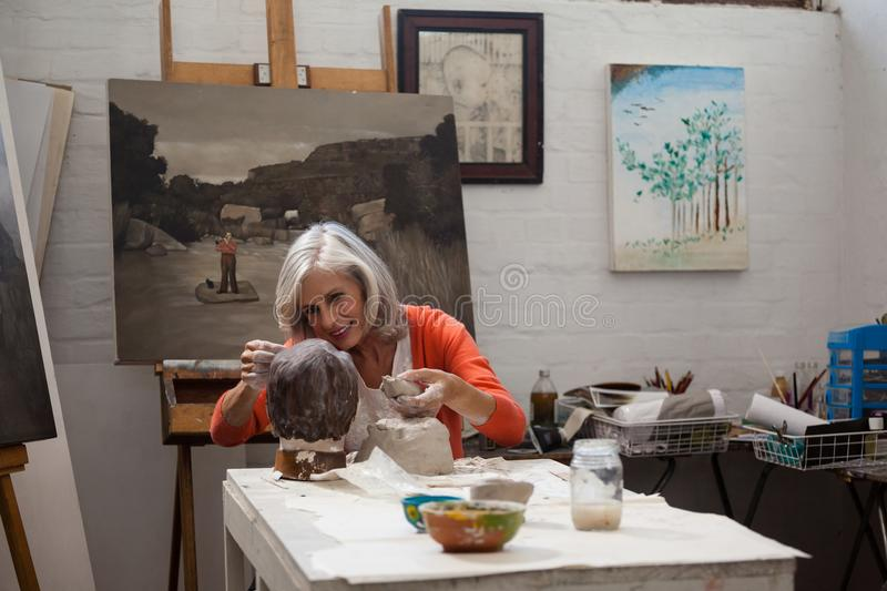 Attentive senior woman making a clay sculpture stock images