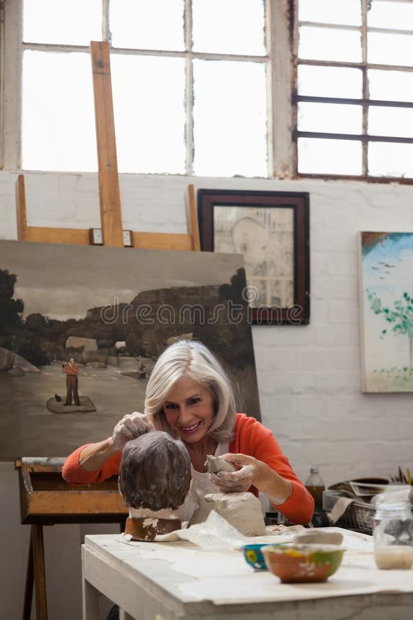 Attentive senior woman making a clay sculpture stock image