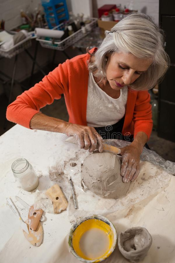 Attentive senior woman shaping a molded clay stock photo