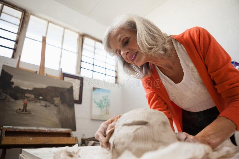 Attentive senior woman shaping a molded clay stock photos