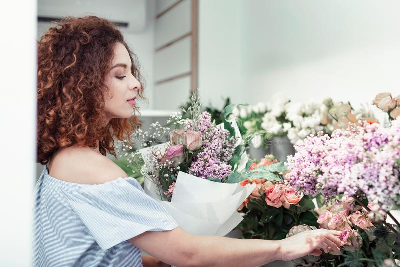 Attentive short-haired woman observing flowers presented on her storage royalty free stock photography