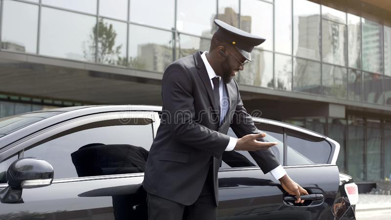 Attentive taxi driver politely opening car door, inviting client to sit down. Stock photo stock image