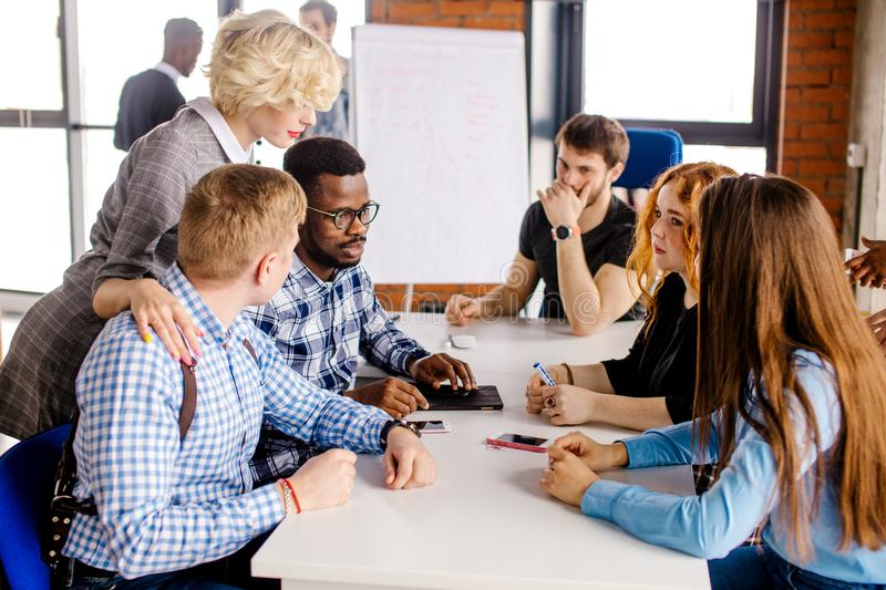 Attentive tutor is giving ear to each member of team. Attentive blond tutor is giving ear to each member of team in the room with panorama window royalty free stock image