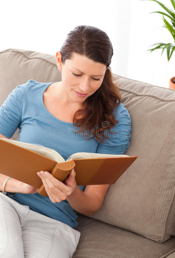 Download Attentive Woman Reading A Book Sitting On Her Sofa Stock Image - Image: 17278089