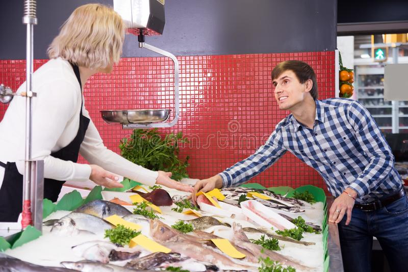 Attentive woman selling fish to male customer in store. Mature attentive women selling fish to male customer in store stock image