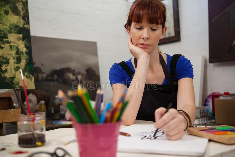 Attentive woman sketching in drawing book royalty free stock photography