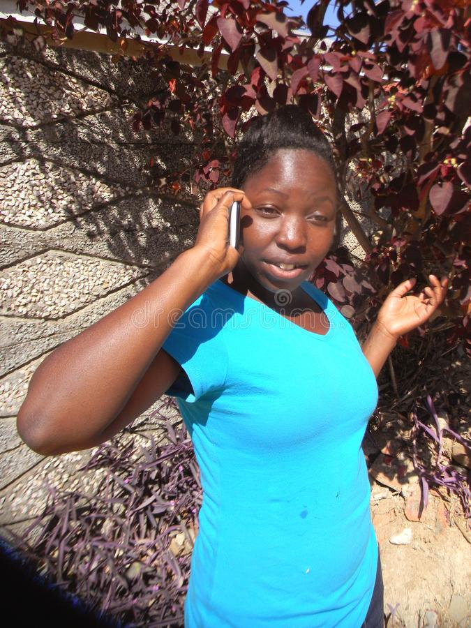 Attentive young African woman speaking on cellphone stock photos