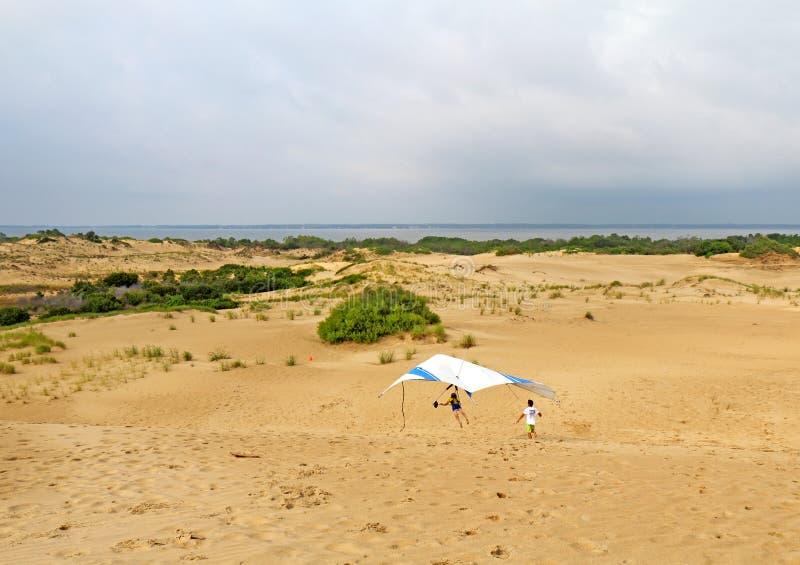 Atterraggio dello studente del deltaplano sulle dune di sabbia in Nord Carolina immagini stock
